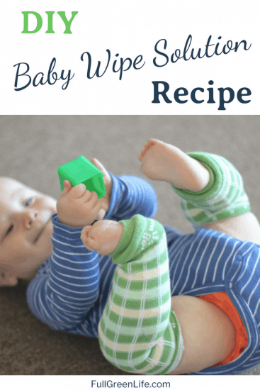 image of baby laying on the floor holding a green block with hands with text-DIY Baby Wipe Solution Recipe