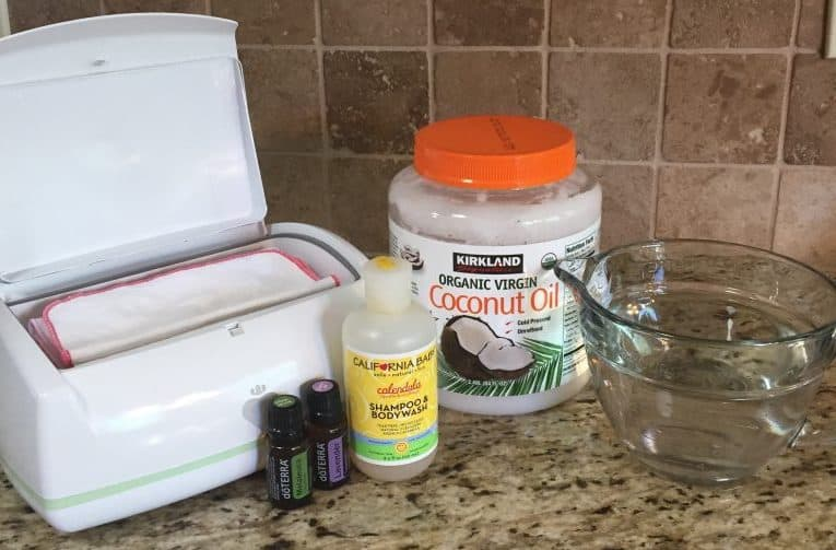 Baby wipe solution supplies: Wipes warmer, cloth wipes, coconut oil, California Baby Wash liquid, glass pitcher, DoTERRA lavender and melaleuca oils