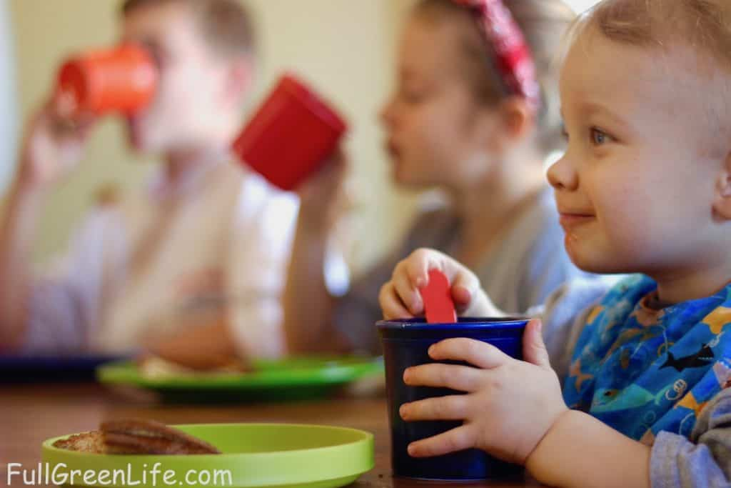 toddler eating at a table with older kids in the background. He is spooning soup from a cup and smiling