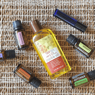 Doterra bottled oils lemon, lavender, melaleuca, geranium, and frankincense, blue glass rollerball bottle, and Trader Joe's bottle of jojoba oil