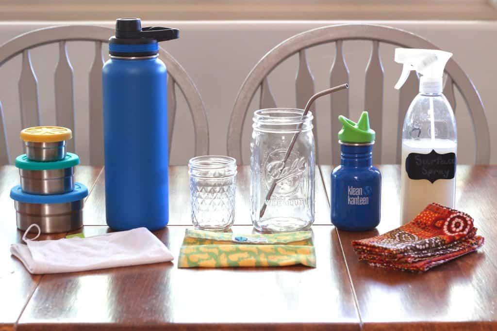 Left to right on wooden kitchen table-Ecolunchboxes set of three round food storage tins stacked, blue insulated stainless steel water bottle, glass jelly jar, 1 qt Ball mason jar, blue Klean Kanteen sippy cup, homemade surface spray bottle, fine mesh produce bag, Planetwise cloth sandwich bag, cloth napkins