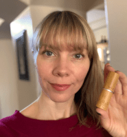 the author wearing lip color and holding bamboo lipstick tube