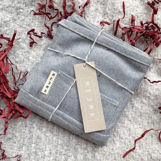 folded denim waist apron with string tied around it and MEEMA brand tag