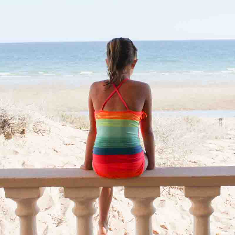 girl in swimsuit sitting on railing facing out toward the sea