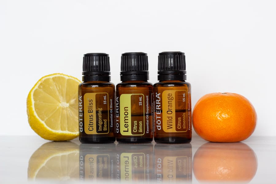 bottles of doterra citrus bliss, lemon, and wild orange pictured beside a half of a lemon and a small orange