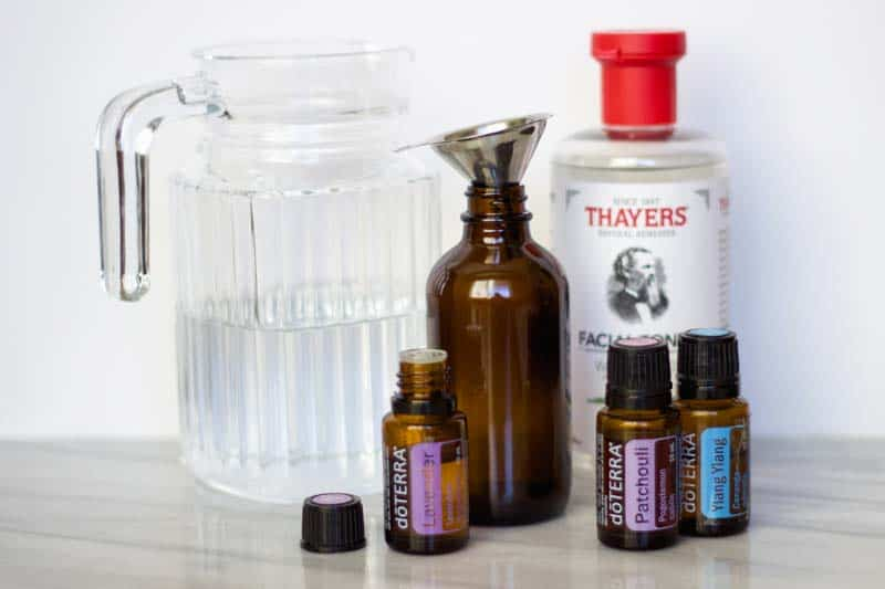 ingredients to make diy room spray: distilled water, Thayer's witch hazel, essential oils, funnel, 4-ounce glass spray bottle