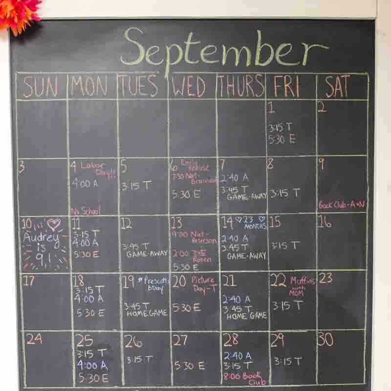 chalkboard wall calendar with calendar and schedule filled in with colored chalk