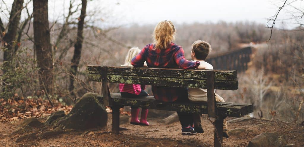mom with two kids on a bench