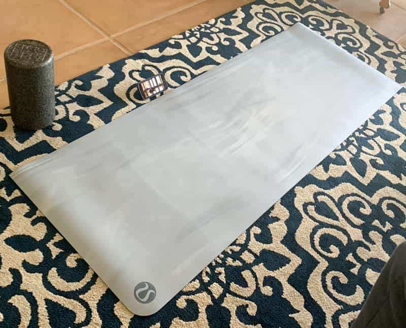 yoga mat on an area rug, with a foam roller and an iphone beside it